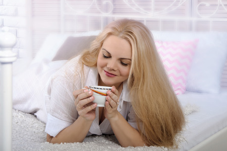 a white robe: Girl lying in bed with a cup of coffee. She is dressed in a white robe, it has the blonde long hair, she is lying on her stomach. Concept: lifestyle, health and beauty. Stock Photo