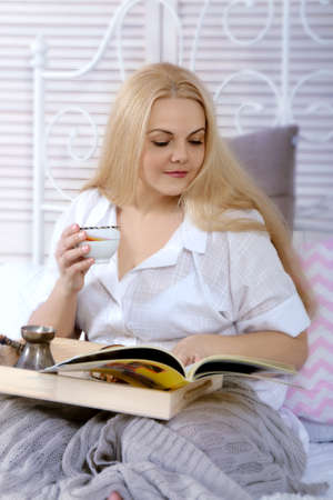 a white robe: Girl has breakfast in bed. She is dressed in a white robe, she is sitting with a tray on her lap, drinking coffee and reading a magazine. Concept: lifestyle, health and beauty.