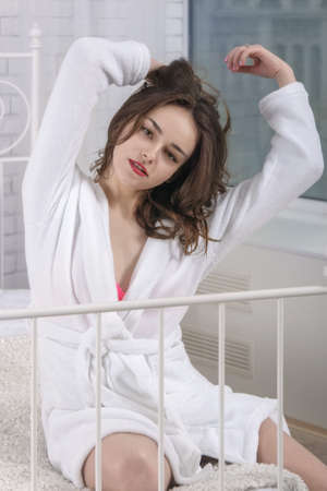 a white robe: Girl woke up in a white bed in the morning. She is dressed in a white robe, her eyes closed and she stretches with pleasure. Concept: lifestyle, health and beauty.