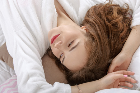 a white robe: Girl woke up in a white bed in the morning. She is dressed in a white robe, her eyes closed and she lies on her back throwing her hands behind her head. Concept: lifestyle, health and beauty.