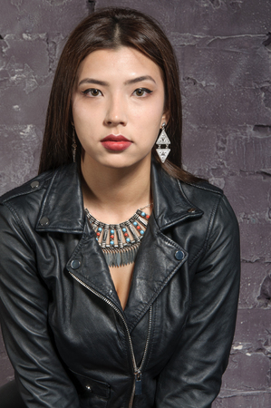 body jewelry: Asian girl wearing a black jacket over a body posing against a background of brown brick wall in the studio. There is ethnic jewelry around her neck.