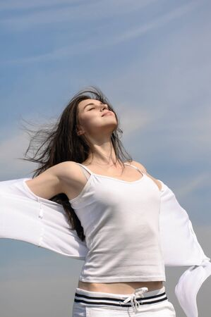 Girl breathes in fresh air on a blue sky background. She stands her arms to the side and her hair fluttering in the wind. She is wearing in a white loose-fitting clothing. Concept: freedom, health, cleanliness.