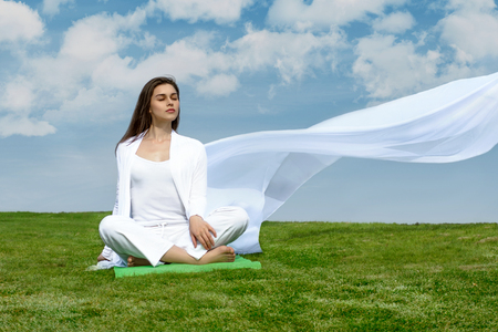 flutter: Girl sitting relaxed on the grass against the blue sky. She is wearing in a white loose clothes, which flutter in the wind. Concept: freedom, health, cleanliness.