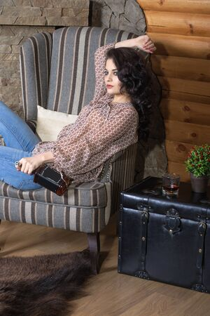 sits on a chair: Girl has a rest in a country house. She sits in a chair and she is holding a bottle of whiskey in her hand. Concept: rest, drink, holiday Stock Photo