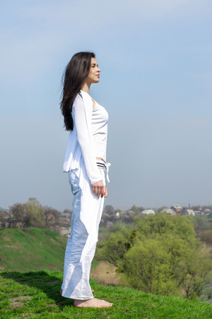 Girl doing yoga exercise standing on a hill against the sky background. Wind waves her hair and white clothes. Concept: relaxation, harmony and health. Stock Photo