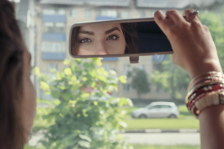 rearview: Woman looking at her reflection in the rearview mirror of car. Concept: beauty, fashion, transportation