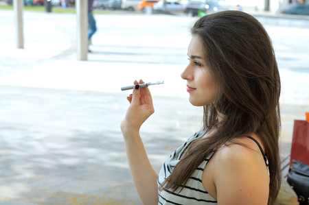 Woman smokes electronic cigarette. She sits in a park with shopping bags. Stock Photo - 60671920
