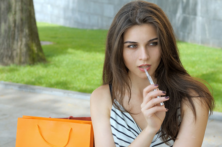 Woman smokes electronic cigarette. She sits in a park with shopping bags. Stock Photo