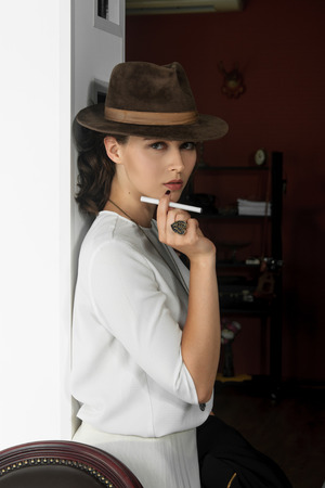 e365539ff0e37  60671867 - Muchacha con estilo en un sombrero en su cabeza que sostiene un  cigarrillo electrónico en su mano. Ella tiene el pelo castaño y está usando  una ...