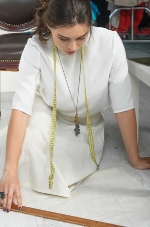 coming up with: Designer clothes sitting on the floor coming up with clothes. She has brown hair and is wearing a light blouse. On her neck hangs a ribbon tape measure, and on the floor lay a pair of scissors and paper.