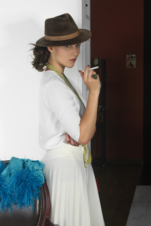 Stylish girl smokes electronic cigarette. She has brown hair and is wearing a light blouse and a brown hat. On her neck hangs a tape measure ribbon