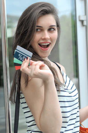 Woman is pleased to get a discount. She is holding a plastic card, while standing near the shop door.