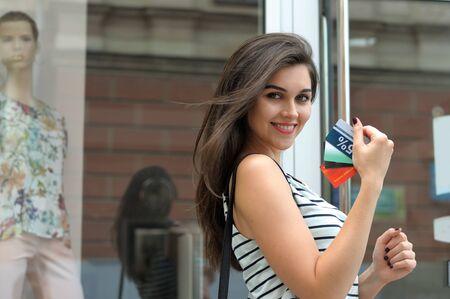 buen trato: La muchacha consigui� un buen negocio. Sonrisas que la celebraci�n de tarjeta de descuento en la mano contra el cristal del escaparate