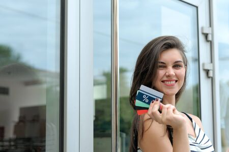 buen trato: Girl got a good deal. She smiles holding discount card in her hand against the glass storefront