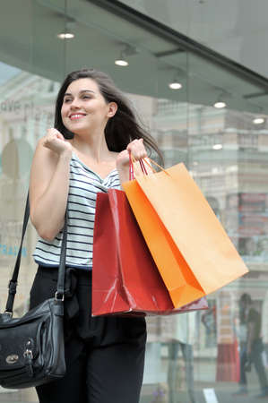 Girl happy near the glass storefront. She is wearing striped shirt, and she holds shopping bags in her hand
