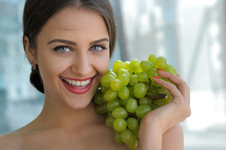 Beautiful turkish woman posing with a bunch of grapes and smiling. Close-up portrait of a girl with bared shoulders against a gentle blue background.