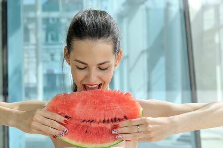 Beautiful girl with bared shoulders posing with a slice of red watermelon