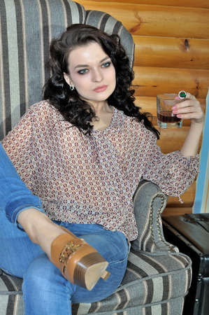 country house style: Girl sits relaxed in a chair and drinking whiskey in a country house Stock Photo