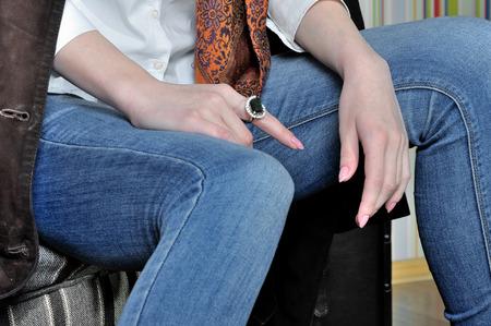 jeans apretados: Primer plano de pantalones vaqueros en el modelo de las piernas. Llevaba unos vaqueros ajustados oscuros azules, una camisa blanca y una chaqueta de gamuza. Foto de archivo