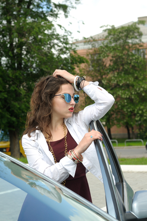 Girl leans on the door of his car. She has long hair and wearing a burgundy dress Stock Photo
