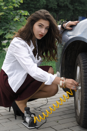 girl in burgundy dress: Girl pumps up the tires of her car by the compressor. She has long hair and wearing a burgundy dress