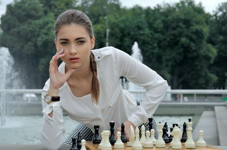 jugando ajedrez: Mujer jugando al ajedrez al aire libre. Ella tiene una piel lisa y está vestida con una blusa a cuadros y pantalones blancos. Foto de archivo