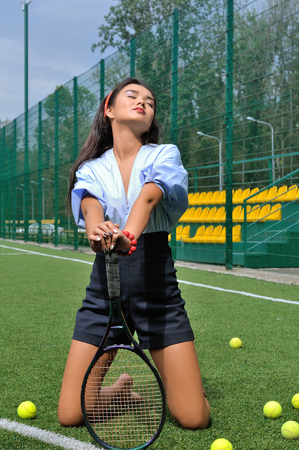 woman kneeling: Woman kneeling on the tennis court relying on the racket. She is wearing a blue shirt, dark blue shorts and high-heeled shoes. Stock Photo
