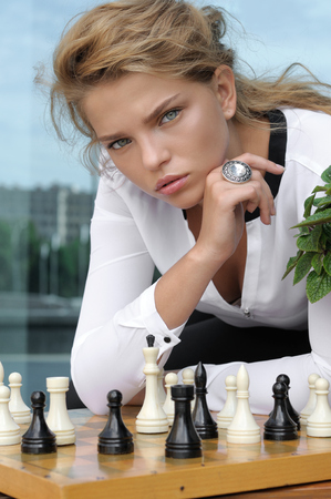 Fashion model posing near the chess board with pieces outdoors.