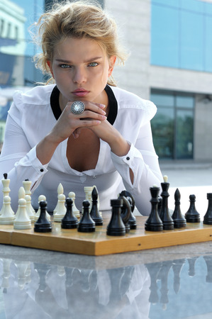 Girl playing chess outdoors. She has long blonde hair and wearing a white shirt