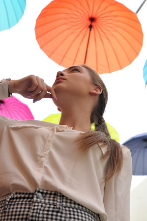 Girl posing under colorful umbrellas, are suspended outdoors. She is wearing a white shirt and plaid pants Stock Photo
