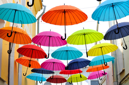 Multicolored umbrellas hanging on strings between buildings