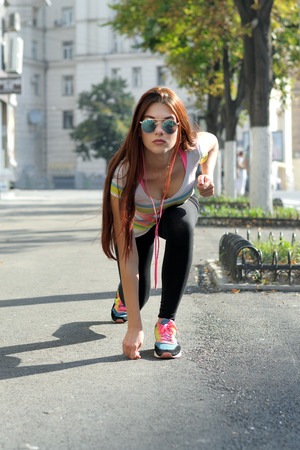 run down: Girl is going to run down the street and listening to music through headphones. She has long red hair, she is wearing a striped shirt.