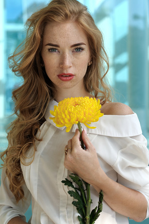 Girl who is holding a yellow flower in her hand has long red hair and freckles on her face. She is dressed in a white blouse against a background of blue glass, in which the city is reflected. Stock Photo