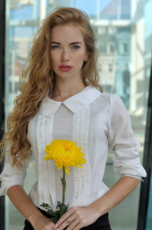 Girl posing with a yellow flower. She has long red hair and lots of freckles on her face. She is dressed in formal clothes - a business suit.