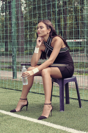 Girl sits on a chair with a water bottle in her hand near the net on the tennis court. She is dressed in shorts, a blouse. Racquet lying on her lap