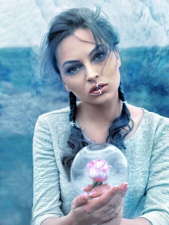Woman holds a glass flask in the frost with a rose inside. Stylization photo in a fantasy style.