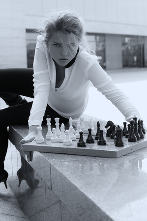 aggressively: Girl aggressively playing chess. Black and white photo in vintage style. Stock Photo