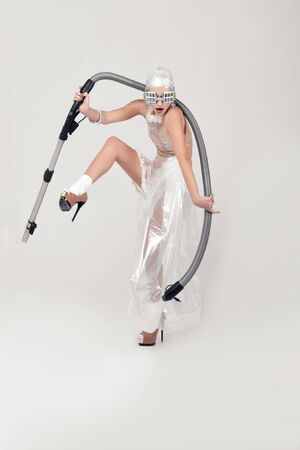 Girl arches holding a vacuum cleaner hose in her hands. She is dressed in an unnatural clothes made of transparent cellophane. The concept of the ambiguity of new materials for the environment and common sense