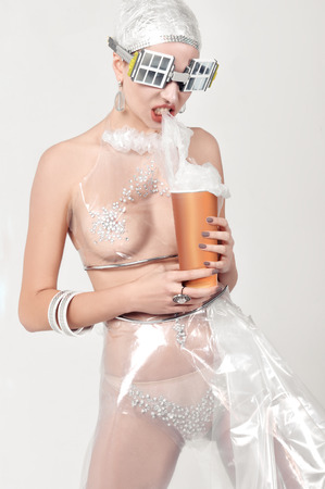 Girl eats plastic, instead of popcorn. She is dressed in an unnatural clothes made of transparent cellophane and preposterous glasses. The concept of the ambiguity of new materials to the environment.