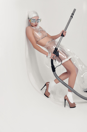 Girl leaning against the wall while holding a vacuum cleaner hose in her hands. She is dressed in an unnatural clothes made of transparent cellophane. The concept of the ambiguity of new materials for the environment and common sense