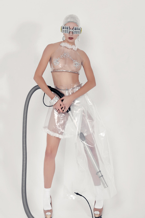 Girl posing while holding a vacuum cleaner hose in her hands. She is dressed in an unnatural clothes made of transparent cellophane. The concept of the ambiguity of new materials for the environment and common sense