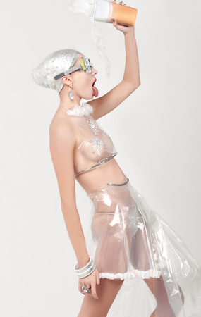 Girl drinks water made of cellophane from the cup. She is dressed in an unnatural clothes made of transparent cellophane and preposterous glasses. The concept of the ambiguity of new materials to the environment.
