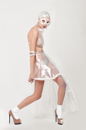 Girl moves unnaturally. She is dressed in an unnatural clothes made of transparent cellophane and preposterous glasses. The concept of the ambiguity of new materials to the environment.