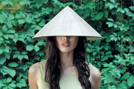 Portrait of a girl in a straw hat in the form of a cone, which is worn by women of Asian countries