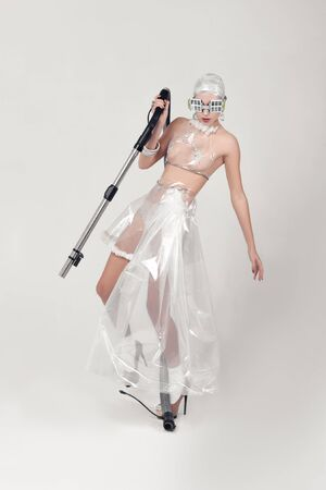 Girl holds a vacuum cleaner hose in her hands. She is dressed in an unnatural clothes made of transparent cellophane. The concept of the ambiguity of new materials for the environment and common sense Stock Photo