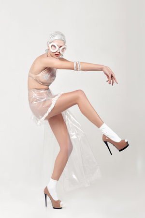 Woman moves unnaturally. She is dressed in an unnatural clothes made of transparent cellophane and preposterous glasses. The concept of the ambiguity of new materials to the environment.