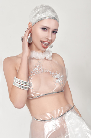Woman holds decoration in her mouth. She is dressed in an unnatural clothes made of transparent cellophane. The concept of the ambiguity of new materials for the environment and common sense Stock Photo