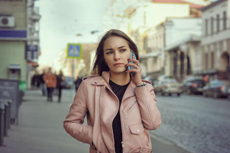 frowns: Attractive girl talking on the phone while walking on the sidewalk in the city. She is unhappy with the conversation and she frowns. It is cold and she is dressed in a leather pink jacket. Stock Photo