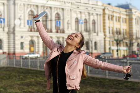 Cheerful girl spinning with joy that bought a tablet. She laughs with her hands in different directions against the background of the city.