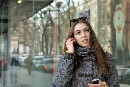 Girl inserts the earpiece into her ear. In the other hand she holds a smartphone with music records. Stock Photo
